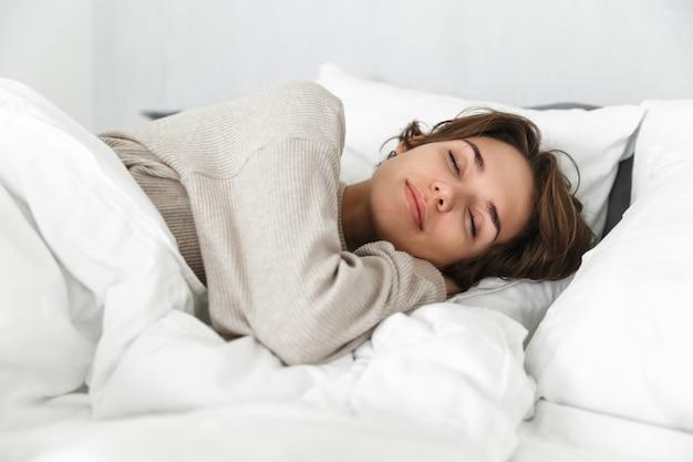 Uśmiechnięta młoda dziewczyna relaksując się w łóżku rano