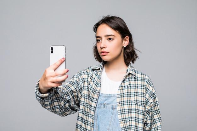 Uśmiechnięta młoda dziewczyna robi połączenie wideo na smartfonie