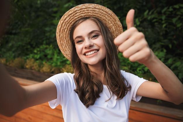 Uśmiechnięta młoda dziewczyna robi selfie z wyciągniętą ręką w parku na świeżym powietrzu, pokazując kciuki do góry