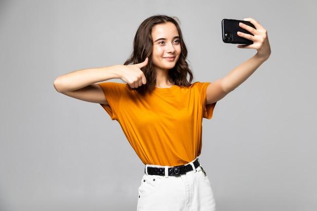 Uśmiechnięta młoda dziewczyna robi selfie zdjęcie na smartfonie na szarej ścianie