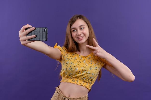 Uśmiechnięta młoda dziewczyna robi znak pokoju i bierze selfie na odosobnionej fioletowej ścianie