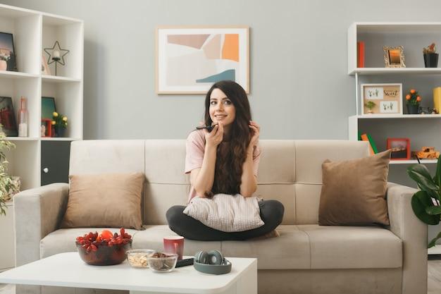 Uśmiechnięta młoda dziewczyna rozmawia przez telefon, siedząc na kanapie za stolikiem kawowym w salonie