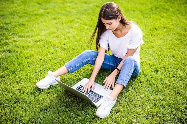 Uśmiechnięta młoda dziewczyna siedzi na trawie z laptopem