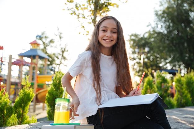 Uśmiechnięta młoda dziewczyna siedzi outdoors z notatnikiem i sokiem