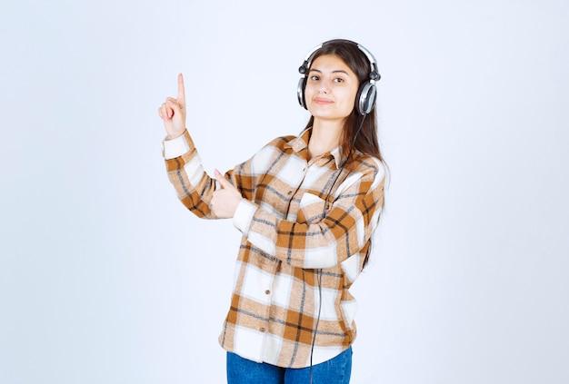 Uśmiechnięta młoda dziewczyna słucha piosenki i wskazuje w hełmofonach.