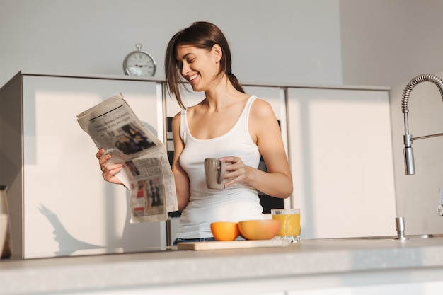 Uśmiechnięta młoda dziewczyna stojąc w kuchni rano, czytając gazetę, pijąc herbatę