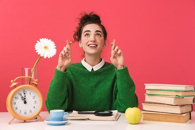 Uśmiechnięta młoda dziewczyna student nerd, wskazując i patrząc w górę siedząc przy stole