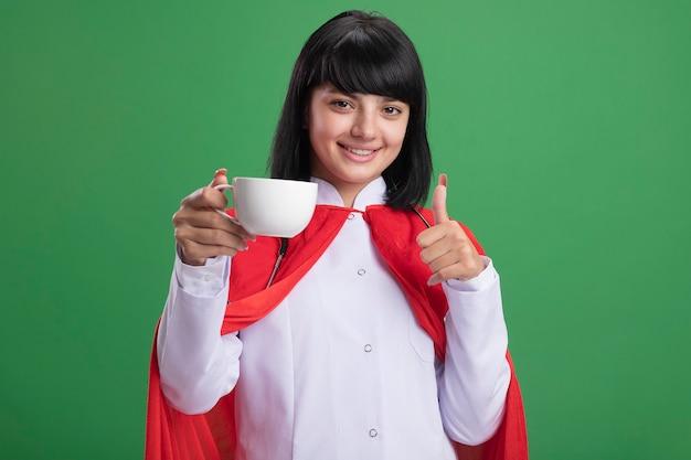 Uśmiechnięta młoda dziewczyna superbohatera ubrana w stetoskop z medycznym szlafrokiem i peleryną, trzymając kubek herbaty, pokazując kciuk do góry na białym tle na zielono