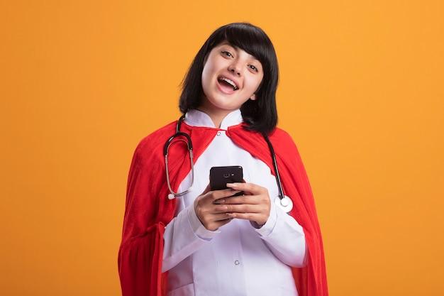 Uśmiechnięta młoda dziewczyna superbohatera ubrana w stetoskop z medycznym szlafrokiem i peleryną, trzymając telefon na białym tle na pomarańczowej ścianie