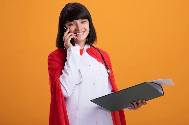 Uśmiechnięta młoda dziewczyna superbohatera w stetoskopie z szatą medyczną i płaszczem trzymająca schowek mówi przez telefon odizolowany na pomarańczowej ścianie