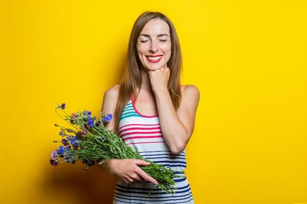Uśmiechnięta młoda dziewczyna trzyma kwiaty z zamkniętymi oczami
