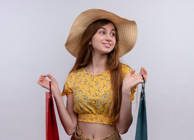 Uśmiechnięta młoda dziewczyna trzyma papierowe torby, patrząc na prawą stronę na na białym tle białej ścianie
