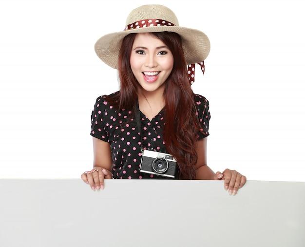 Uśmiechnięta młoda dziewczyna trzyma pustą białą deskę