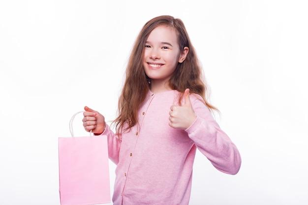 Uśmiechnięta młoda dziewczyna trzyma torbę na zakupy i pokazuje kciuk do góry.