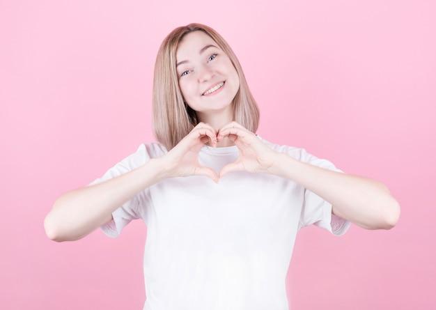 Uśmiechnięta młoda dziewczyna w białej koszulce pokazuje serce obiema rękami, znak miłości. koncepcja na walentynki na różowym tle