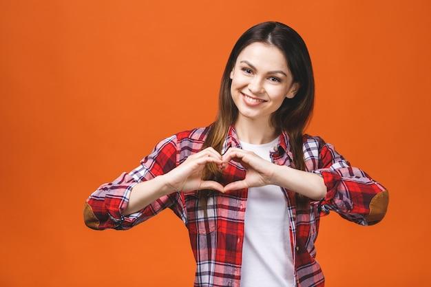 Uśmiechnięta młoda dziewczyna w przypadkowym pokazuje sercu z dwa rękami, miłość znak. pojedynczo na żółtym tle.