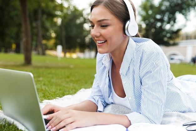 Uśmiechnięta młoda dziewczyna w słuchawkach spędzająca czas