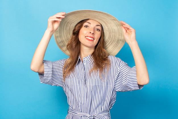 Uśmiechnięta młoda dziewczyna w sukni i kapeluszu, trzyma kapelusz z rękami na błękitnej ścianie. pojęcie wakacji, lata i podróży