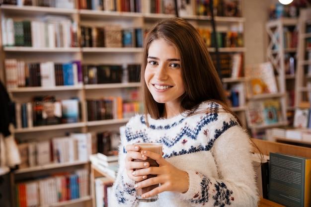 Uśmiechnięta młoda dziewczyna w swetrze z filiżanką kawy w bibliotece