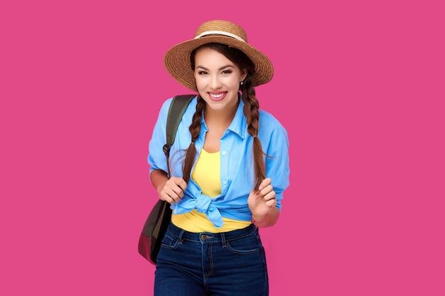 Uśmiechnięta młoda dziewczyna w ubranie i słomkowy kapelusz na różowym tle na białym tle. studentka z plecakiem. strzał studio