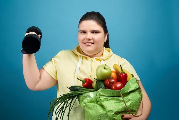 Uśmiechnięta młoda dziewczyna w żółtym swetrze patrząc na kamery i trzymając paczkę z owocami i warzywami z jednej strony i hantlami na drugiej. ładna gruba kobieta wybiera zdrowe produkty i sport