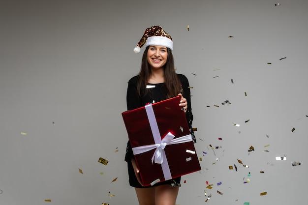 Uśmiechnięta młoda dziewczyna z dużym świątecznym prezentem wskazująca ręką na pustą przestrzeń z świątecznym konfetti na ...