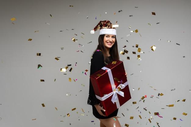 Uśmiechnięta młoda dziewczyna z dużym świątecznym prezentem wskazująca ręką na pustej przestrzeni z świątecznym konfetti na szarym tle