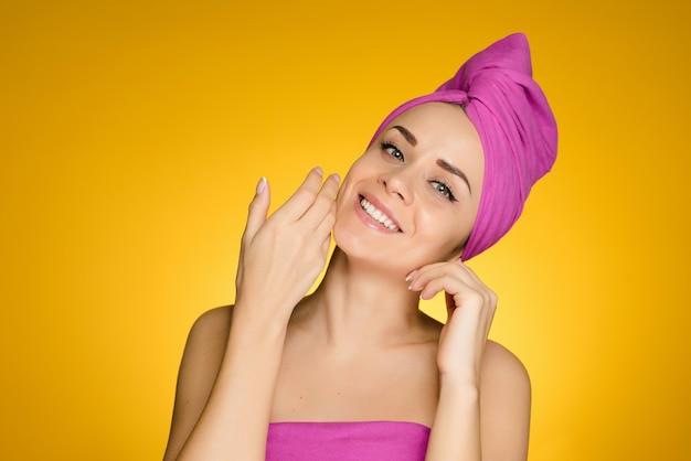Uśmiechnięta młoda dziewczyna z różowym ręcznikiem na głowie korzystająca ze spa, czysta skóra