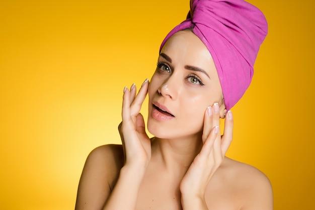 Uśmiechnięta młoda dziewczyna z różowym ręcznikiem na głowie nakłada krem nawilżający na twarz