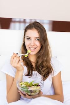 Uśmiechnięta młoda dziewczyna zjada jej śniadanie sałatka jarzynowa w łóżku