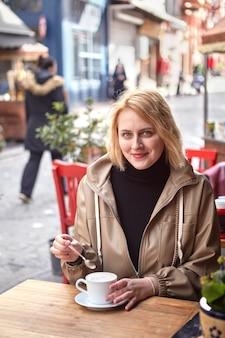Uśmiechnięta młoda europejska kobieta pije kawę w ulicznej kawiarni w żydowskiej dzielnicy fatih w stambule.