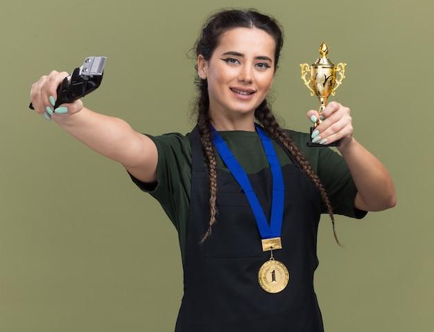 Uśmiechnięta młoda fryzjerka w mundurze i medalu, trzymająca puchar zwycięzcy i trzymająca maszynkę do strzyżenia włosów w aparacie na białym tle na oliwkowozielonej ścianie