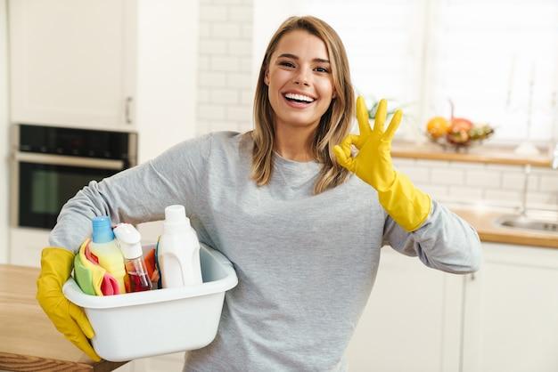 Uśmiechnięta młoda gospodyni domowa w rękawiczkach trzymająca butelki do mycia i pokazująca znak ok w nowoczesnej kuchni