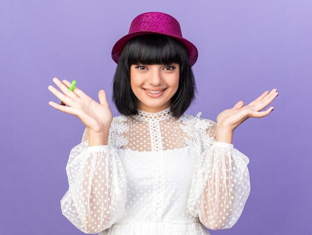 Uśmiechnięta młoda imprezowa dziewczyna w imprezowym kapeluszu trzymająca imprezowy róg, patrząc na przód pokazujący pustą rękę odizolowaną na fioletowej ścianie