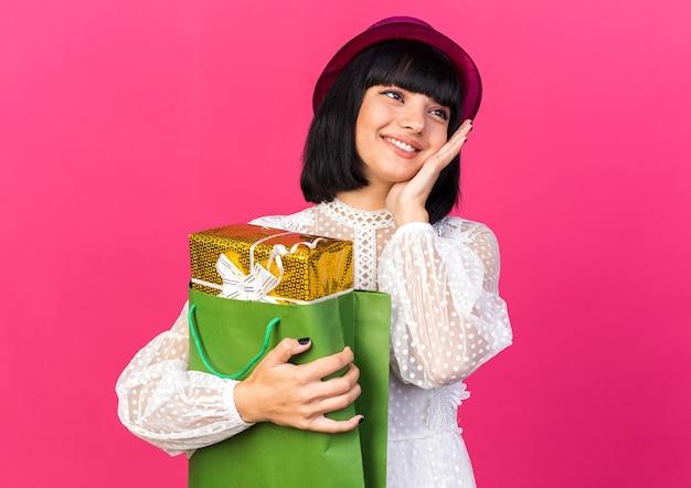 Uśmiechnięta młoda imprezowa kobieta w imprezowym kapeluszu trzymająca pakiet prezentów w papierowej torbie, trzymając rękę na twarzy, patrząc na bok odizolowany na różowej ścianie