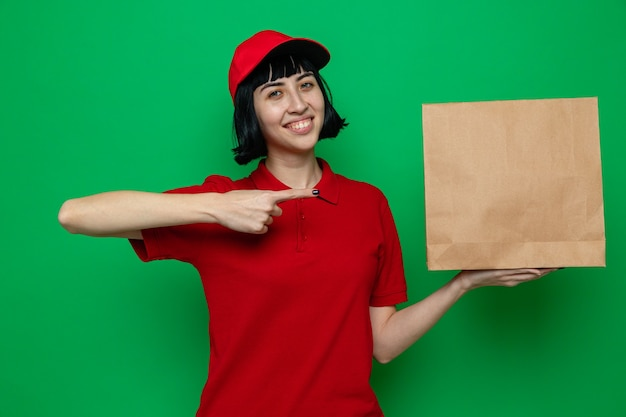 Uśmiechnięta młoda kaukaska dziewczyna dostarczająca jedzenie, trzymająca i wskazująca na papierowe opakowanie żywności