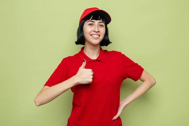 Uśmiechnięta młoda kaukaska dziewczyna dostarczająca kciuki w górę