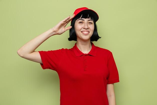 Uśmiechnięta młoda kaukaska dziewczyna-dostawca trzymająca rękę blisko głowy, salutując