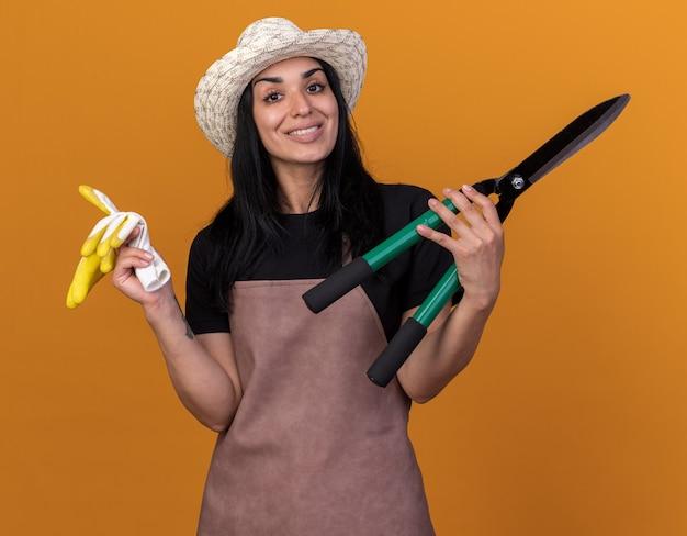 Uśmiechnięta młoda kaukaska dziewczyna ogrodniczka w mundurze i kapeluszu trzymająca nożyce do żywopłotu i rękawiczki ogrodnika odizolowane na pomarańczowej ścianie