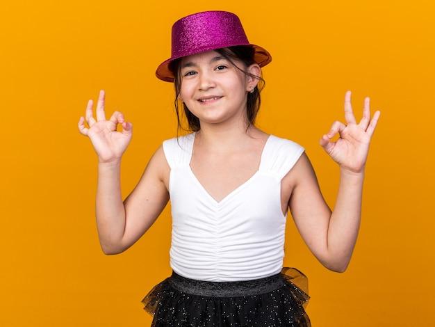 Uśmiechnięta młoda kaukaska dziewczyna w fioletowym kapeluszu imprezowym gestykuluje ok znak na pomarańczowej ścianie z miejscem na kopię