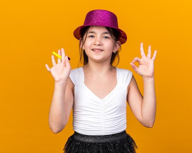 Uśmiechnięta młoda kaukaska dziewczyna w fioletowym kapeluszu imprezowym trzymająca gwizdek i gestykulujący ok znak odizolowany na pomarańczowej ścianie z kopią przestrzeni