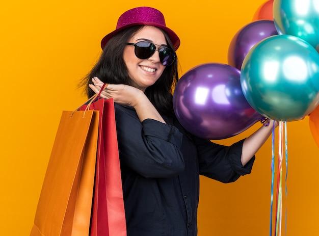 Uśmiechnięta młoda kaukaska dziewczyna w imprezowym kapeluszu i okularach przeciwsłonecznych, stojąca w widoku z profilu, trzymająca pęk balonów i papierowych toreb na ramieniu na białym tle na pomarańczowej ścianie