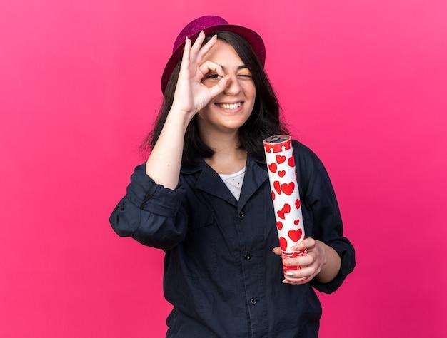 Uśmiechnięta młoda kaukaska dziewczyna w imprezowym kapeluszu trzymająca armatę konfetti robi gest spojrzenia na różowej ścianie