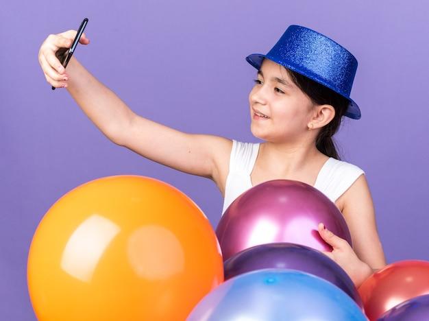 Uśmiechnięta młoda kaukaska dziewczyna w niebieskim kapeluszu imprezowym biorąca selfie na telefon stojący z balonami z helem odizolowanych na fioletowej ścianie z kopią przestrzeni