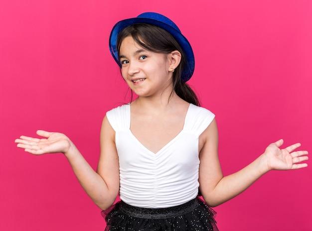 Uśmiechnięta młoda kaukaska dziewczyna w niebieskim kapeluszu imprezowym, trzymająca otwarte ręce na różowej ścianie z miejscem na kopię