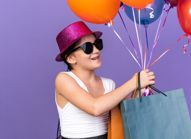Uśmiechnięta młoda kaukaska dziewczyna w okularach przeciwsłonecznych z fioletowym kapeluszem imprezowym trzymająca torby na zakupy i patrząc na balony z helem odizolowane na fioletowej ścianie z miejscem na kopię