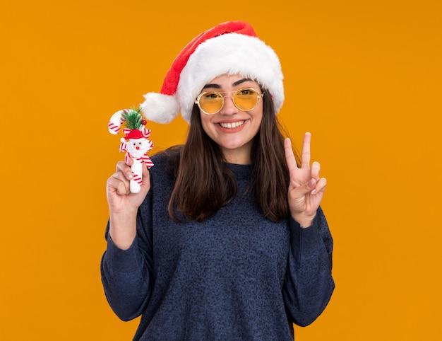 Uśmiechnięta młoda kaukaska dziewczyna w okularach przeciwsłonecznych z santa hat gestykuluje znak zwycięstwa i trzyma trzcinę cukrową odizolowaną na pomarańczowej ścianie z kopią przestrzeni