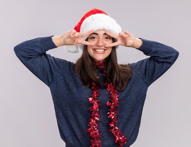 Uśmiechnięta młoda kaukaska dziewczyna z santa hat i girlandą wokół szyi gestykuluje znak zwycięstwa palcami odizolowanymi na białej ścianie z kopią miejsca