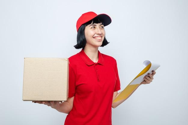 Uśmiechnięta młoda kaukaska dziewczynka trzymająca karton i schowek, patrząc na bok