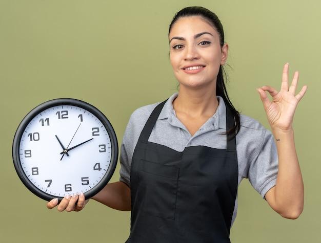 Uśmiechnięta młoda kaukaska fryzjerka w mundurze trzymająca zegar, patrząca na przód, robiąca znak ok na oliwkowozielonej ścianie